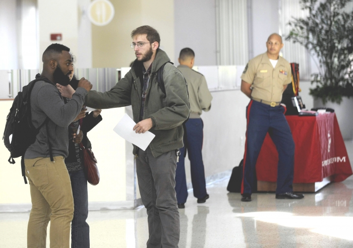 """Gage Lacharite, center, head of the local branch of Students for a Democratic Society, prepares to hand out """"counter-recruiting"""" fliers at USF's Marshall Student Center. JAY CONNER"""