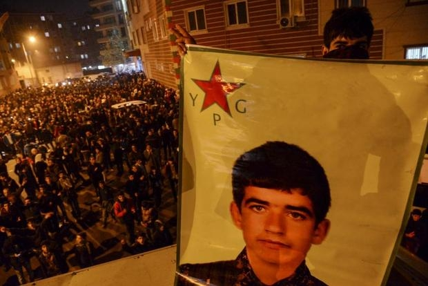 A Kurdish youth holds a picture of a YPG (People's Protection Units) fighter killed in Kobane during a celebration in Diyarbakir on 26 January 2015 (AFP)