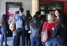 High school students line up to use the new SkoolLive kiosks